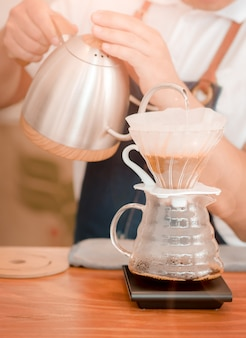 Barista holding pours hot boiled water in a coffee pot