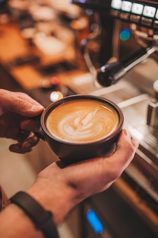 Barista holds a cup of coffee in his hands