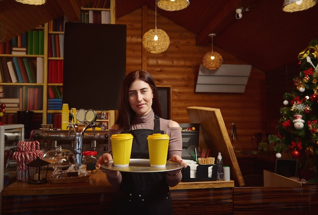Barista holds a tray with yellow takeaway cardboard cups of coffee and showing it at camera