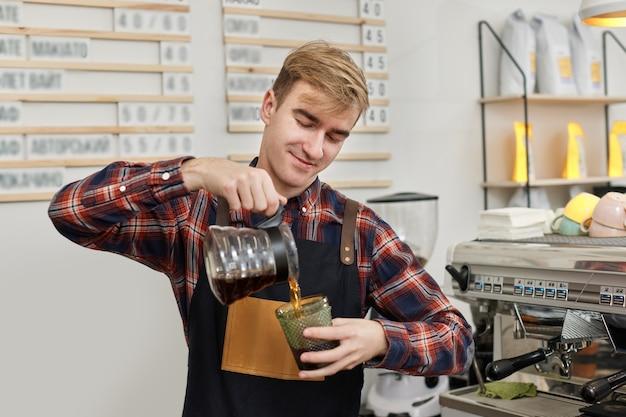 앞치마를 입은 바리스타가 컵에 신선한 커피를 붓는다