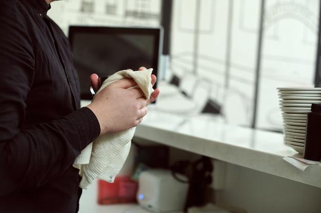 Бариста в черной рубашке вытирает руки белым полотенцем за стойкой бара. крупным планом