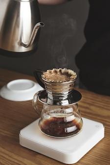 블랙 스웨트 샷의 바리 스타는 여과 된 커피 / 실버 찻 주전자를 흰색 단순한 무게의 아름다운 투명한 크롬 드립 커피 메이커에 준비합니다. 카페 숍의 두꺼운 나무 테이블에있는 모든 것. 증기