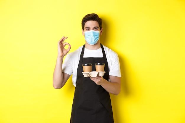 의료용 마스크와 검은 앞치마를 입은 바리 스타는 안전을 보장하고 테이크 아웃 커피 컵을 들고 ok 사인, 노란색 벽을 보여줍니다.