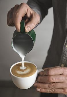 바리 스타는 빈 흰색 컵에 카푸치노를 준비하고 있으며 우유 거품을 심장 모양으로 흘립니다. 카페 숍.