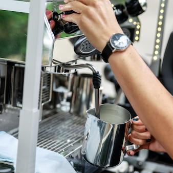 바리 스타가 커피를 준비하고 있습니다. 카푸치노 또는 라떼 용 우유 찌기 및 거품 만들기.