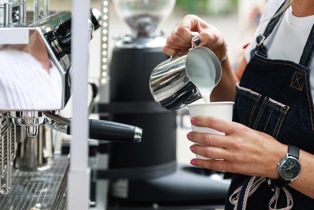 Бариста готовит кофе. приготовление на пару и вспенивание молока для капучино или латте.