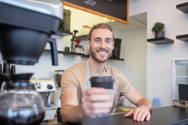 バリスタ。コーヒーを丁寧に差し出しているカフェのカウンターでうれしそうなひげを生やした若い男性バリスタ