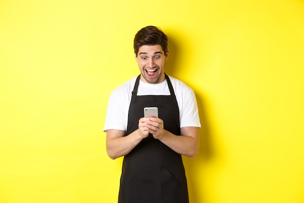 Barista looking surprised as reading message on mobile phone, standing in black apron against yellow background.