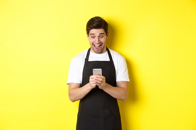 Barista looking surprised as reading message on mobile phone standing in black apron against yellow ...