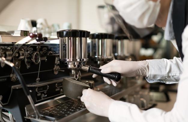 바리 스타는 뜨거운 커피를 만들고, 작업자는 현대 커피 머신으로 커피를 만듭니다.