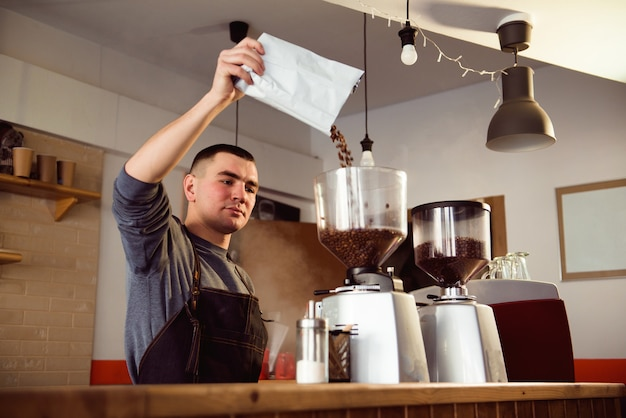 Barista makes espresso in cafe. barista grind beans with coffee machine. coffee grinder grinding roasted beans in powder.