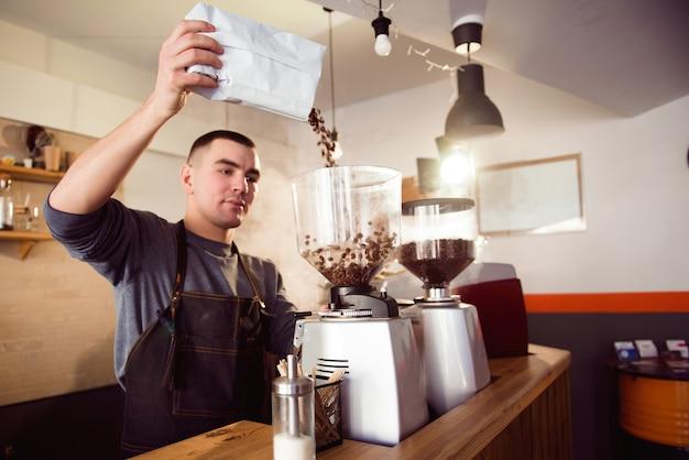 Бариста делает эспрессо в кафе. бариста молоть фасоль с кофемашиной. кофемолка помола жареные бобы в порошок.