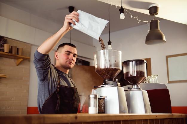 Barista는 카페에서 에스프레소를 만듭니다. 바리 스타는 커피 머신으로 콩을 갈아서 만듭니다. 볶은 콩을 분말로 분쇄하는 커피 분쇄기.
