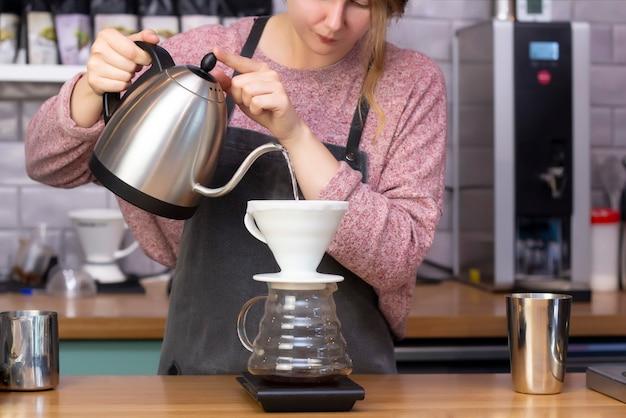 バリスタはじょうごを使ってエスプレッソを作ります。証明者でコーヒーを作るプロセス。やかんからフィルター漏斗を通してコーヒーをこぼします。