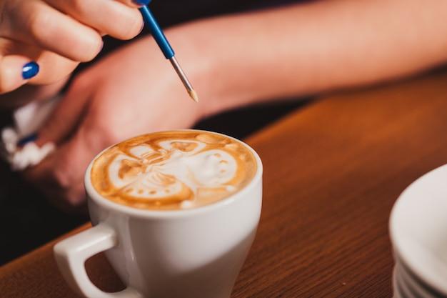 Бариста готовит чашку кофе латте-арт с помощью специального металлического приспособления - latte-art pen tool