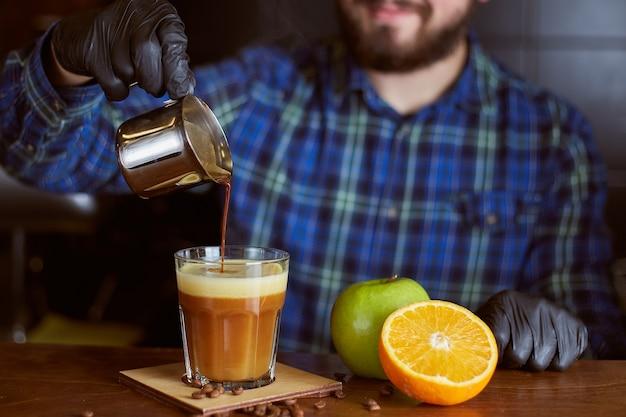 コーヒーカクテルを作るバリスタ。オレンジとアップルジュースのエスプレッソ