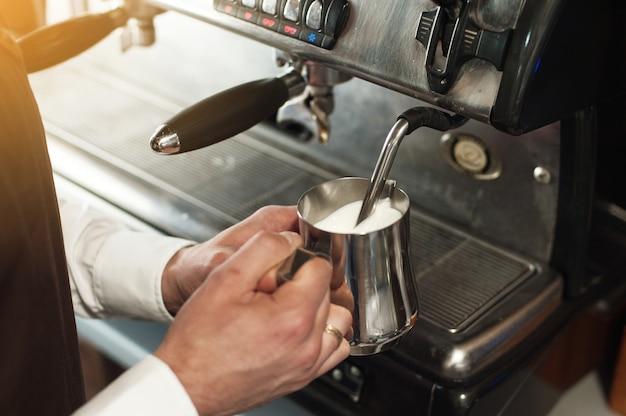 Barista making coffee. preparing milk for cappuccino