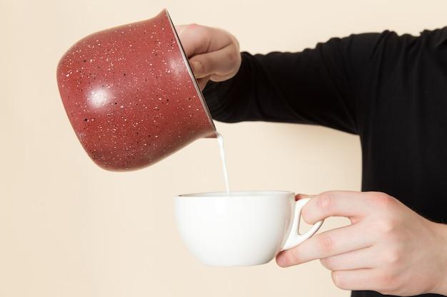 白い机の上に注ぐ牛乳でコーヒーを作るバリスタ