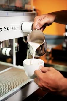 Barista making coffee with milk