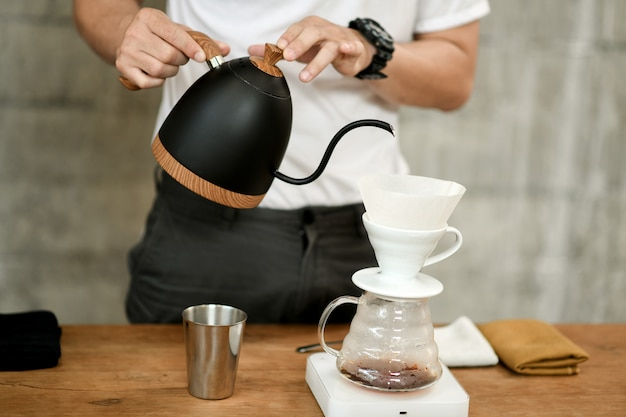 Barista making drip coffee in cafe.