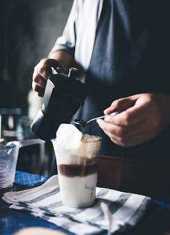 Бариста делает ледяной кофе.