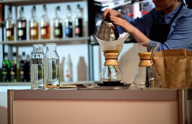 Бариста делает кофе кемекс.