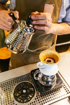 Barista making pour-over coffee with alternative method called dripping.
