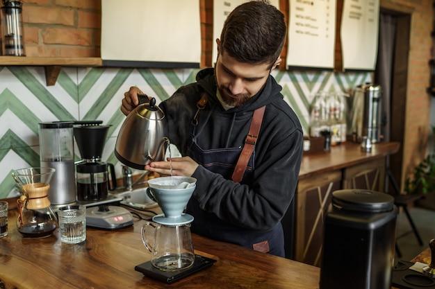 Мужчина barista заваривает одну чашку, а работник кофейни заваривает одну чашку кофе, используя уникальную систему.