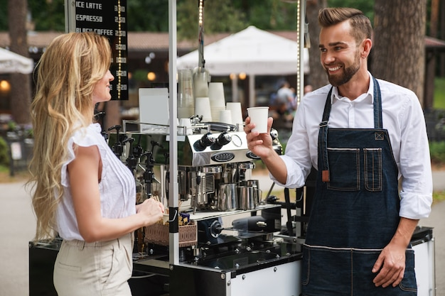 Barista man giving cup of coffee to woman customer in his movable cafe