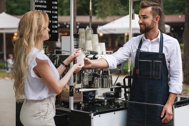 그의 이동식 카페에서 여자 고객에게 커피 한 잔을주는 바리 스타 남자