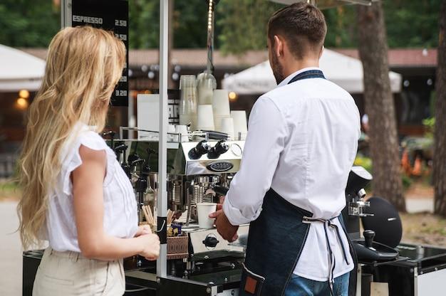 그의 이동식 거리 커피 숍에서 고객을 위해 커피를 만드는 바리 스타 남자
