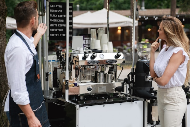 Barista man offer to choose various kinds of coffee to the woman customer in his movable cafe