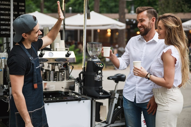 Barista man selling coffee to young couple in the movable coffee shop on the street