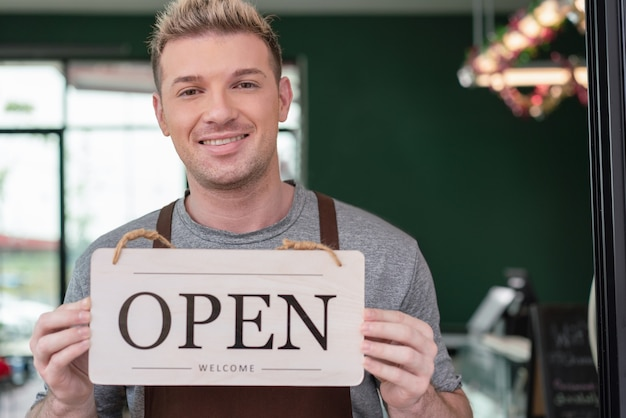 バリスタのオーナーが笑顔でオープンサインを持ち、コーヒーショップの顧客を歓迎