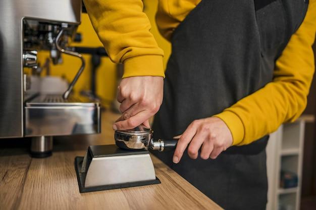 バリスタがマシンのカップにコーヒーを詰める