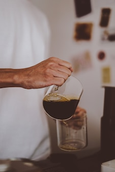 Barista pour coffee into glass after brewing coffee, home brewing style