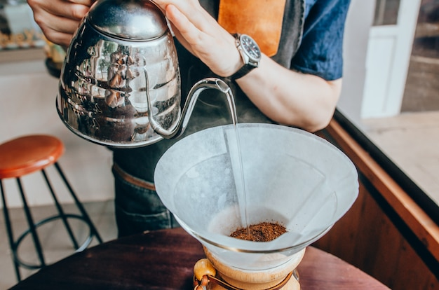 Barista pouring boiling water from kettle