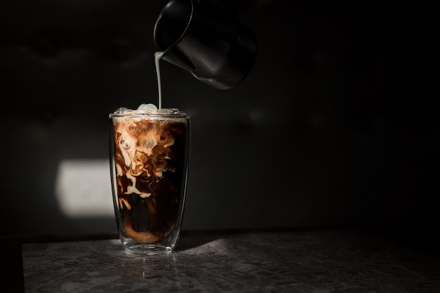 Barista pouring coffee in glass