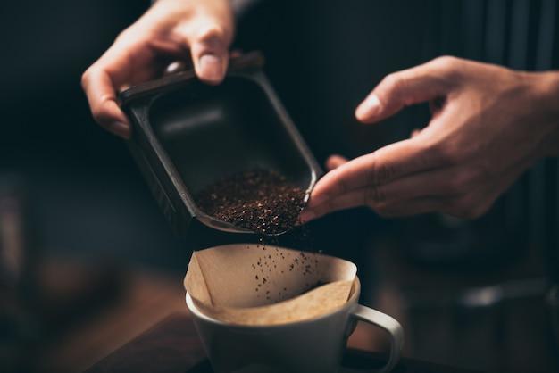 바리 스타는 커피 분쇄기에서 드리퍼로 커피 가루를 붓고 카페에서 신선한 커피를 만듭니다.