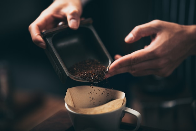 Barista pouring coffee powder from a coffee grinder to a dripper to make fresh coffee in the cafãƒâ©.