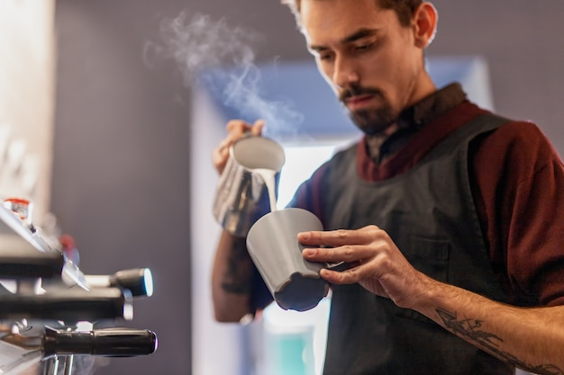 Barista pouring hot milk into cup