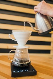 Бариста наливает горячую воду на кофейный фильтр