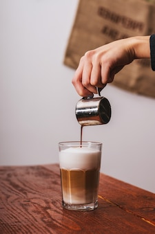 Barista pouring milk in capuccino coffee in coffeeshop