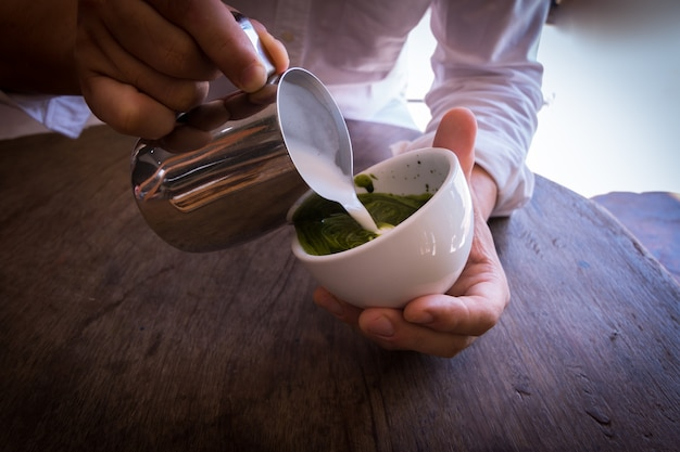 Barista pouring milk in coffee cup make green tea late art