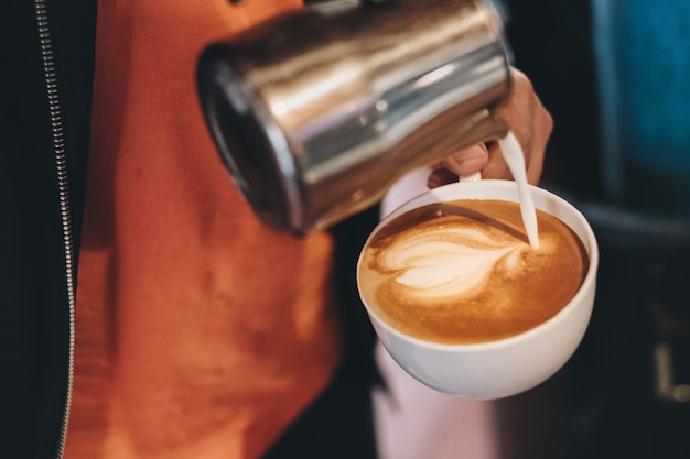 Barista pouring milk on coffee cup making heart