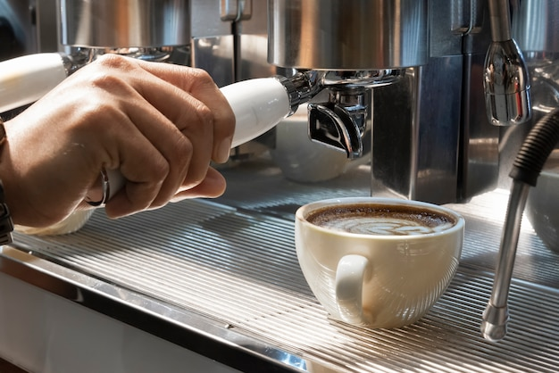 Barista pouring milk from coffee machine in milk jar to prepare latte foam in coffee shop close up