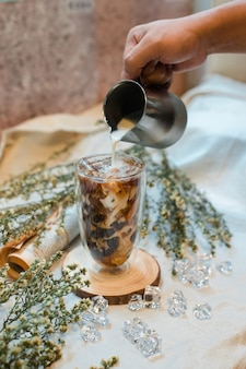 Бариста наливает молоко в стакан кофе со льдом