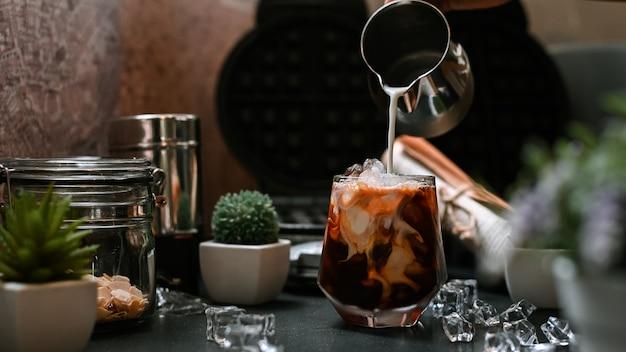 アイスコーヒーのグラスに牛乳を注ぐバリスタ