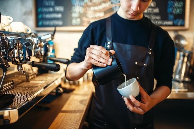 Бариста наливает сливки в чашку кофе