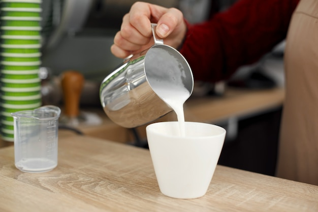 Barista pours milk from metal pot to white glass cup on wooden table